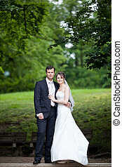 young wedding couple - freshly wed groom and bride posing ...