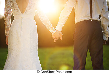 Young wedding couple holding hands as they enjoy romantic ...