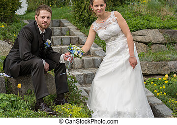 Young wedding couple in garden - Braut haelt mit Braeutigam...