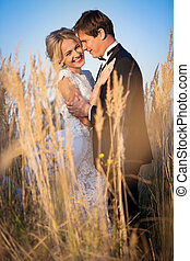 Young wedding couple standing in a field