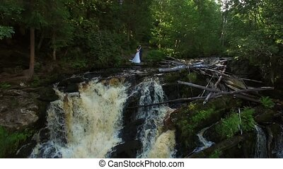 Young wedding couple staying near waterfall