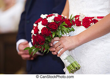 Young wedding couple - Bride and groom in the church holding...