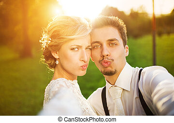 Young wedding couple taking a selfie of themselves as they ...
