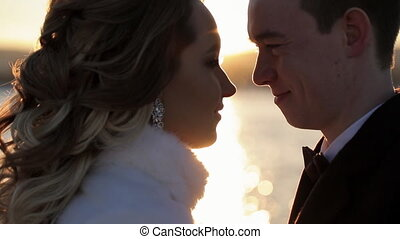 Young wedding couple walking in snowy winter outdoors to make photos