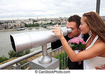 Young wedding couple with tourist binoculars