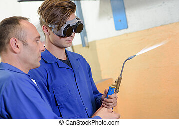 young welder with a teacher