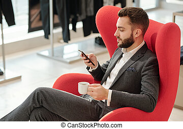 Young well-dressed businessman with cup of tea texting in smartphone
