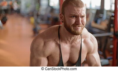 Young white bodybuilder training biceps in the gym