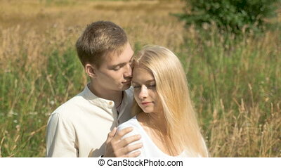 Young white couple on date. The guy gently caresses his girlfriend. She closes her eyes