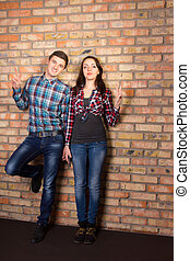 Young White Couple Posing at Brick Wall