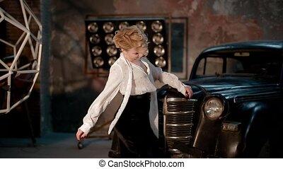 Young white female dancer in studio near the retro car