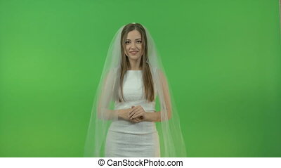 Young white girl in a bride dress, on a green background.