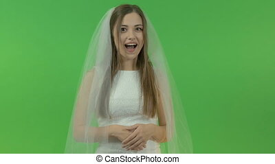 Young white girl in a bride dress, on a green background. She shows an engagement ring on her finger