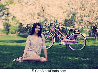 Young white girl with bicycle in spring park