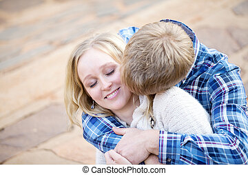 Young white male kissing his fiancé in her neck