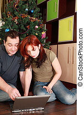 young wife and husband sitting on floor near Christmas tree and looking at laptop's screen, focus on woman
