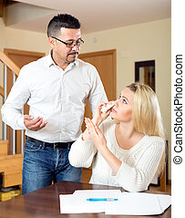 Young wife crying over documents