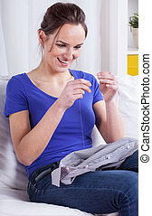 Young wife sewing husband shirt
