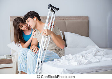 Young wife supporting husband on crutch after injury