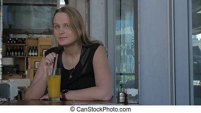Young wistful woman having drink in cafe - Young woman with...