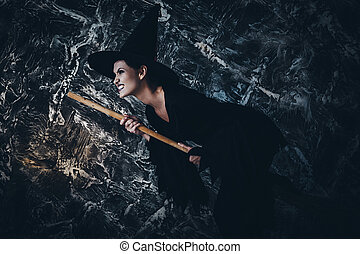 young witch flying on the broomstick