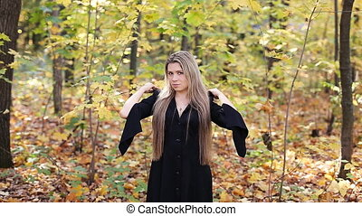 Young witch in a autumn forest