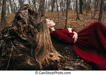 Young witch in the autumn forest - Young woman in red dress...