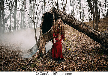 Young witch in the autumn forest