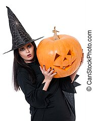 Young witch with halloween pumpkin over white background