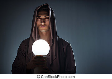 Young wizard with crystal ball in dark room
