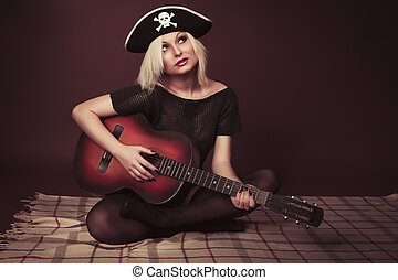 Young woman a guitar in a pirate hat