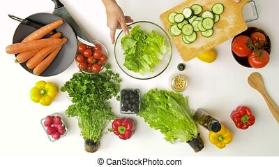 young woman adding cucumber to salad at home - healthy ...