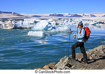 Young woman admires the beauty of the glacial lagoon Jokulsarlon in Iceland