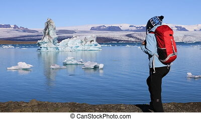 Young woman admires the beauty of the glacial lagoon Jokulsarlon