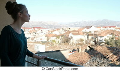 Young woman admires the landscape on balcony in her home....