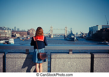 Young woman admiring London skyline - A young woman is...