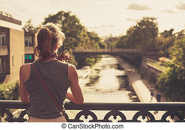 Young woman admiring the sunset from a bridge - A young...