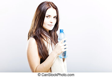 Young woman after fitness with towel and water bottle
