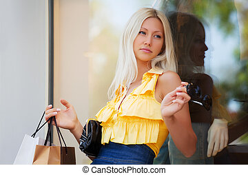 Young woman against a shop window