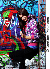 Young woman against wall with graffiti