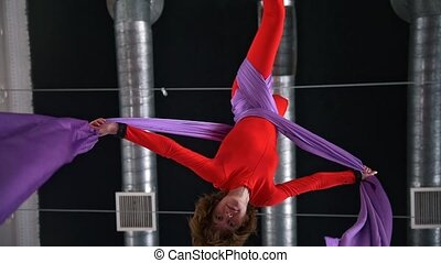 Young woman air gymnast circling on aerial silk in the air...