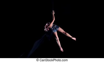Young woman air gymnast on black background