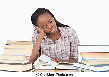 Young woman almost falling asleep while reading against a...