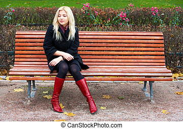 Young woman sitting alone on bench in park, looking down