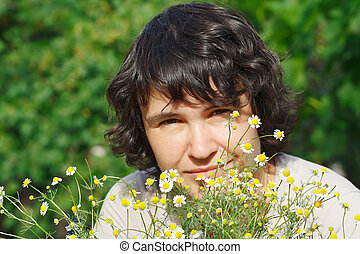 Young woman among the summer daisies outdoors
