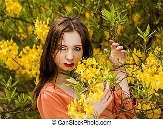 Young woman among yellow flowers