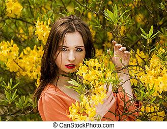 Young woman among yellow flowers