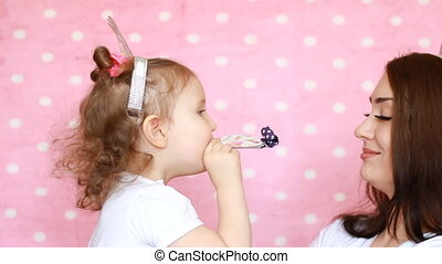 Young woman and a child blowing horns. Happy birthday....