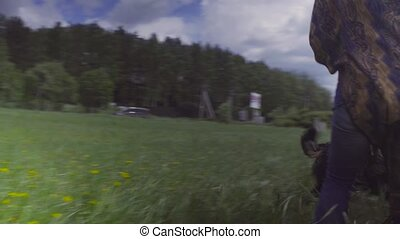Young woman and a dog running on a field