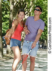 young woman and blind man in the park